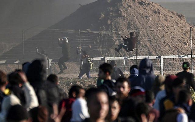 Des Palestiniens escaladent la clôture de sécurité à la frontière avec Israël lors d'affrontements dans l'est de la bande de Gaza, le 8 mars 2019 (Crédit : MAHMUD HAMS / AFP)
