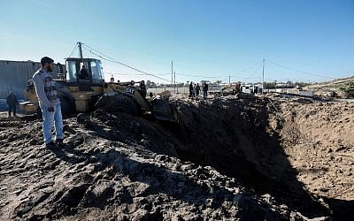 Des Palestiniens nettoient les décombres sur le site d'une frappe israélienne après d'un port maritime en construction à proximité de Khan Younès, dans le sud de la bande de Gaza, le 9 mars 2018 (Crédit : SAID KHATIB / AFP)