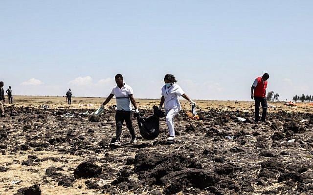 Des équipes de secouristes transportent des sacs mortuaires sur le lieu du crash du Boeing d'Ethiopian Airlines, le 10 mars 2019. (Crédit : Michael TEWELDE / AFP)