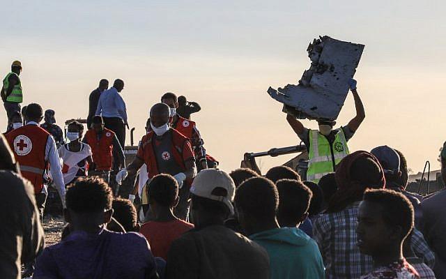Un homme porte un débris d'avion sur le lieu du crash du Boeing d'Ethiopian Airlines, le 12 mars 2019. (Crédit : Michael TEWELDE / AFP))