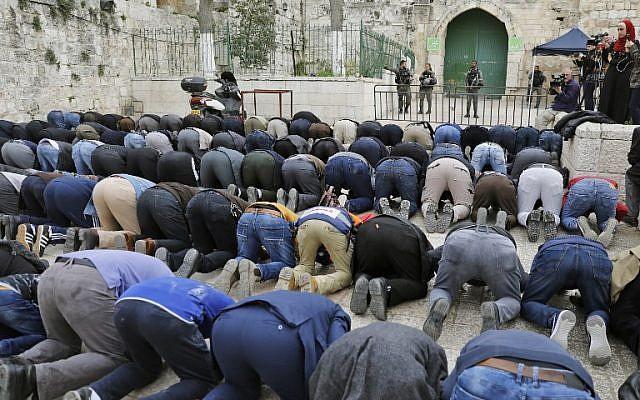 Des fidèles musulmans prient devant une barrière après que la police des frontières a fermé l'une des entrée du mont du Temple, dans la Vieille Ville de Jérusalem, le 12 mars 2019 (Crédit : Ahmad Gharabli/AFP)