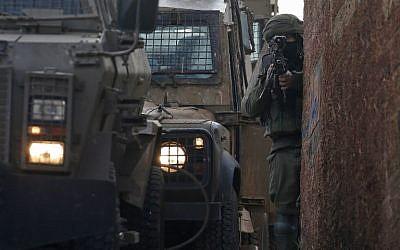 Un soldat israélien monte la garde  pendant une opération de recherche d'un suspect palestinien dans le village de Salem,dans le nord de la Cisjordanie et à l'est de Naplouse, le 18 mars 2019 (Crédit : JAAFAR ASHTIYEH / AFP)