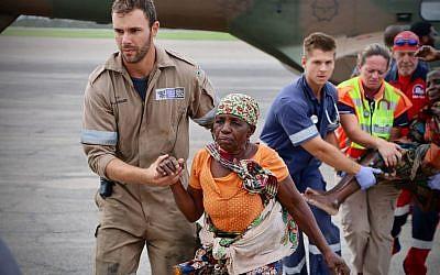 Le 19 mars 2019, à la suite du passage du cyclone Idai, des travailleurs humanitaires escortent les victimes à l'aéroport de la ville côtière de Beira. (Crédit photo : Adrien Barbier / AFP)