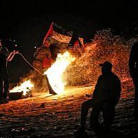 Des manifestants palestiniens durant une manifestation nocturne à proximité de la frontière avec Israël à Rafah, dans le sud de la bande de Gaza, le 19 mars 2019 (Crédit : SAID KHATIB / AFP)