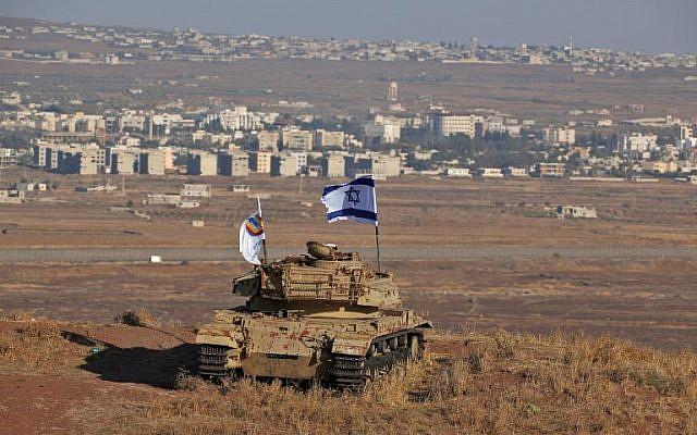 Un drapeau d'Israël flotte sur l'épave d'un char israélien qui se trouve sur une colline du plateau du Golan et qui domine la frontière avec la Syrie, le 18 octobre 2017. (Crédit: JALAA MAREY / AFP)