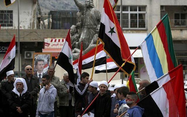 Des habitants du Golan agitent des drapeaux syrien et druze face au portrait du président syrien Bachar al-Assad lors d'une manifestation contre la déclaration du président américain Donald Trump, qui a reconnu sur Twitter le Golan comme appartenant à Israël, dans le village de Majdal Shams, le 23 mars 2019. (Crédit photo : Jalaa MAREY / AFP)