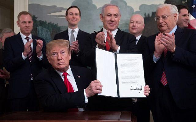 Le président des États-Unis, Donald Trump, présente une proclamation signée et reconnaissant la souveraineté sur le plateau du Golan aux côtés du Premier ministre Benjamin Netanyahu dans la salle de réception diplomatique de la Maison Blanche à Washington, le 25 mars 2019. (Crédit : SAUL LOEB / AFP)