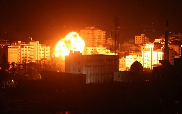 Une boule de feu souffle sur les bâtiments de la ville de Gaza après des représailles israéliennes du 25 mars 2019. (Crédit : Majdi Fathi / AFP)