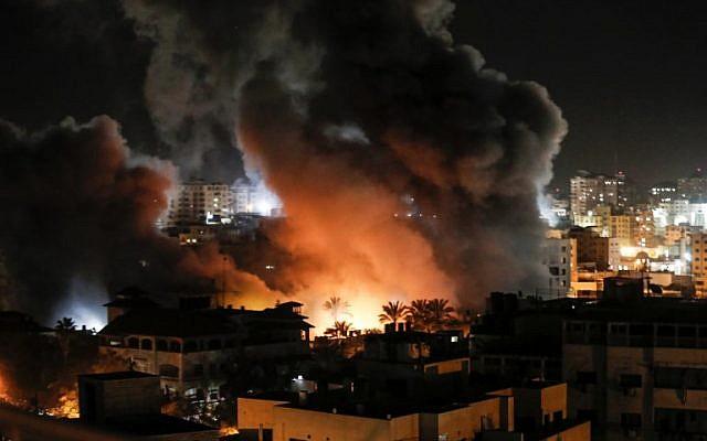 Un feu et de la fumée se propagent au-dessus des bâtiments dans la ville de Gaza après des frappes israéliennes le 25 mars 2019. (Crédit : Mahmud Hams / AFP)