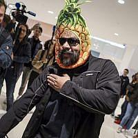 """Dieudonné M'bala M'bala, portant un masque représentant un ananas en référence à son expression négationniste 'shoahananas', fait le geste controversé de la """"quenelle"""" à son arrivée au palais de justice de Paris le 26 mars 2019, devant un public amusé. (Crédit : KENZO TRIBOUILLARD / AFP)"""