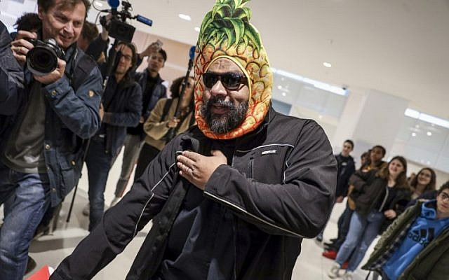 """Dieudonné M'bala M'bala, portant un masque représentant un ananas en référence à son expression négationniste 'shoahananas', fait le geste controversé de la """"quenelle"""" à son arrivée au palais de justice de Paris le 26 mars 2019, devant un public amusé (Crédit : KENZO TRIBOUILLARD / AFP)"""