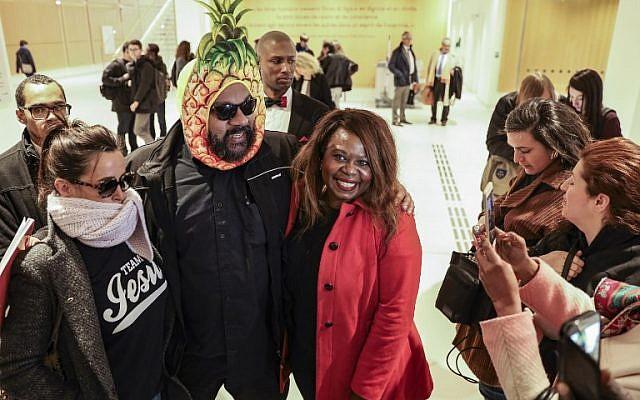 Dieudonné M'bala M'bala, portant un masque représentant un ananas en référence à son expression négationniste 'shoahananas', pose à son arrivée au palais de justice de Paris le 26 mars 2019, (Crédit : KENZO TRIBOUILLARD / AFP)