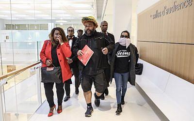 Dieudonné M'bala M'bala, portant un masque représentant un ananas en référence à son expression négationniste 'shoahananas', se dirige vers le palais de justice de Paris le 26 mars 2019, (Crédit : KENZO TRIBOUILLARD / AFP)