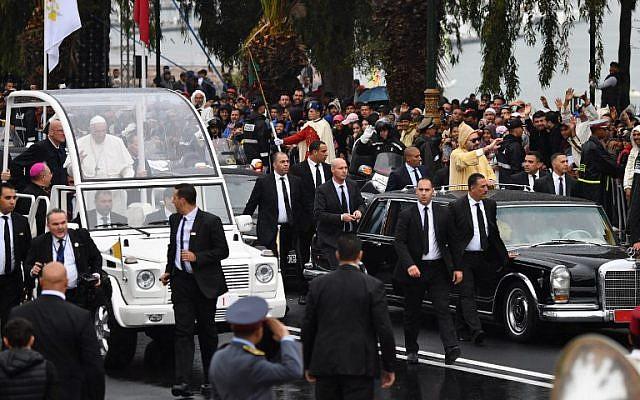 Le roi Mohammed VI, à droite, salue la foule depuis sa voiture lors de l'arrivée du pape Français dans la papamobile lors de l'arrivée du souverain pontife au Maroc, le 30 mars 2019 (Crédit : Alberto Pizzoli/AFP)