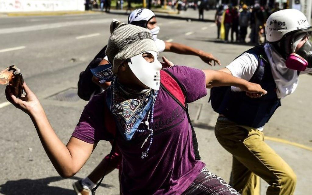 Un militant de l'opposition lance un cocktail Molotov lors d'affrontements avec les forces de sécurité dans la capitale vénézuélienne de Caracas, le 12 août 2017. (AFP Photo/Ronaldo Schemidt)