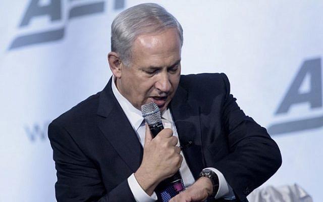 Le Premier ministre israélien Benjamin Netanyahu regarde sa montre en plaisantant dans un discours sur la paix au Moyen-Orient au National Building Museum, le 9 novembre 2015 à Washington, DC. (Crédit : AFP/Brendan SmialowskiI)