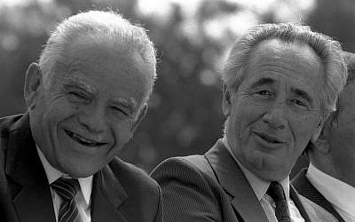 Flashback à l'époque des Premier ministres en rotation : Le Premier ministre Yitzhak Shamir, à gauche, et le ministre des Affaires étrangères Shimon Peres au parc Sacher de Jérusalem pendant une fête de Mimouna, le 15 mars 1988 (Crédit : Nati Harnik / Bureau du Gouvernement)