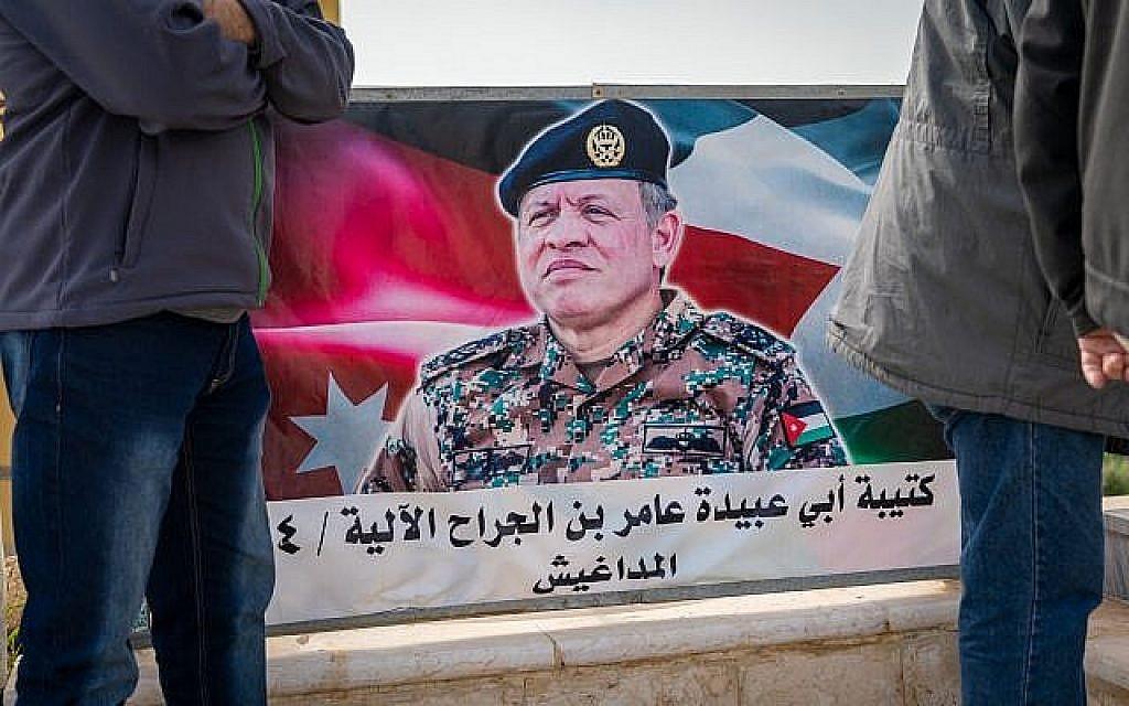 Des touristes israéliens se tiennent devant une affiche du roi Abdallah II de Jordanie sur l'île de la Paix, le 29 janvier 2019. (Luke Tress/Times of Israel)