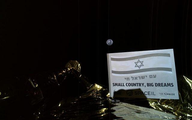 """La photo prise par la sonde Bereshit et diffusée le 24 mars 2019 : une plaque installée sur la paroi externe de la sonde arbore le drapeau national israélien et les phrases """"Am Yisrael Hai"""" (Vive le peuple d'Israël) et """"Petit pays, grands rêves"""", avec le globe terrestre en arrière plan. (Crédit : Bereshit)"""