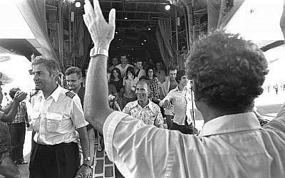 Le ministre israélien des Affaires étrangères de l'époque Yigal Allon (de dos) accueille les passagers et l'équipage d'Air France sauvés dont le pilote Michel Bacos (à gauche) qui descendent d'un avion Hercule de l'armée de l'air israélienne à l'aéroport Ben Gurion en juillet 1976 (Moshe Milner, Service de presse du gouvernement israélien).