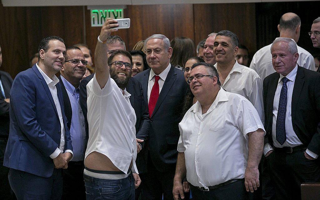 Le député Likud Oren Hazan prend un selfie avec le Premier ministre Benjamin Netanyahu, (au centre), et le député David Bitan, (à droite de Netanyahu), après l'adoption de la loi de l'État-nation à la Knesset, le 19 juillet 2018. (AP Photo/Olivier Fitoussi)