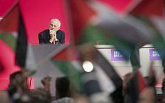 Le dirigeant du Parti travailliste britannique Jeremy Corbyn est assis sur la scène alors que ses partisans agitent des drapeaux palestiniens lors de la conférence annuelle du parti à Liverpool, en Angleterre, le 25 septembre 2018. (Stefan Rousseau/PA via AP)
