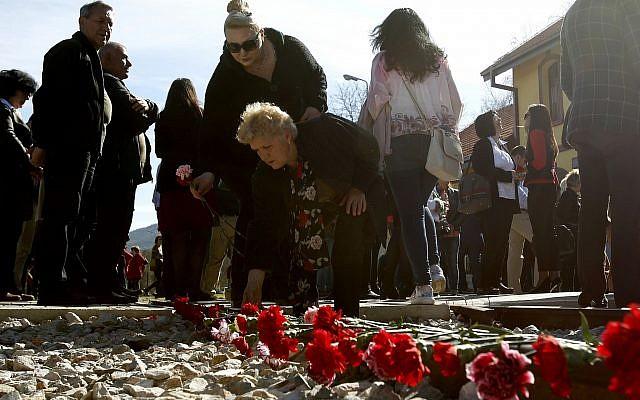 Des fleurs sont posées sur les rails au cours d'une cérémonie de commémoration des victimes de la Shoah à la gare de Bitola, dans le sud de la Macédoine, le 11 mars 2019 (Crédit : AP Photo/Boris Grdanoski)