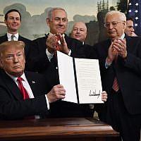 Le président américain Donald Trump présente un décret signé reconnaissant la souveraineté d'Israël sur le plateau du Golan, sous le regard du Premier ministre Benjamin Netanyahu dans la salle de réception diplomatique de la Maison Blanche à Washington, le 25 mars 2019. (AP Photo/Susan Walsh)