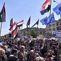 Des Syriens brandissent des portraits de Bashar el Assad durant une manifestation contre la reconnaissance de la souveraineté israélienne sur le plateau duGolan par Donald Trump, le 26 mars 2019. (Crédit : SANA via AP)