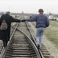 Un couple se tient la main en marchant en équilibre sur les rails de la voie ferrée ayant transporté plus d'un million de personnes vers la mort, au camp de concentration d'Auschwitz-Birkenau, le 26 janvier 1995. (Crédit : AP/Jockel Finck)