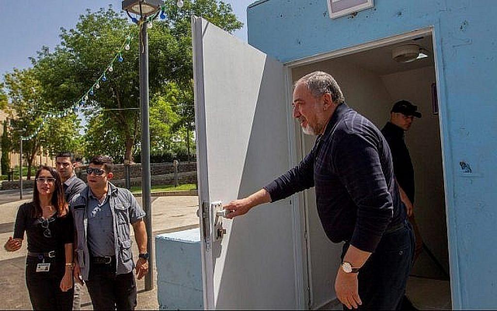 Le ministre de la Défense de l'époque Avigdor Liberman à l'entrée d'un abri anti-aérien lors d'une visite à Katzrin, sur le plateau du Golan, le 11 mai 2018 (Crédit : Basel Awidat/Flash90)
