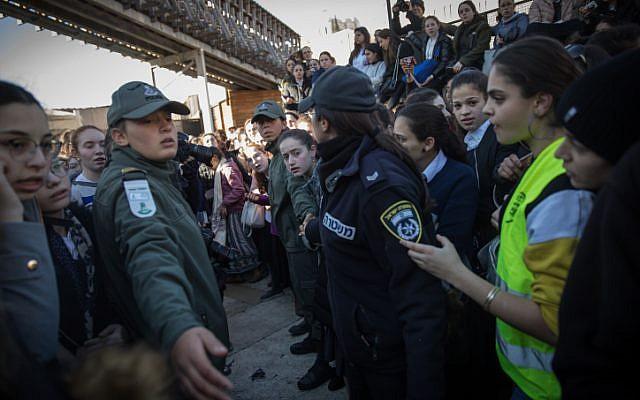 Des garde-frontières aident les membres des Femmes du mur à partir après avoir tenté de mener à bien les prières du mois, alors que des milliers de femmes ultra-orthodoxes s'opposent à elles au mur Occidental, dans la Vieille Ville de Jérusalem, le 8 mars 2019 (Crédit : Hadas Parush/Flash90)