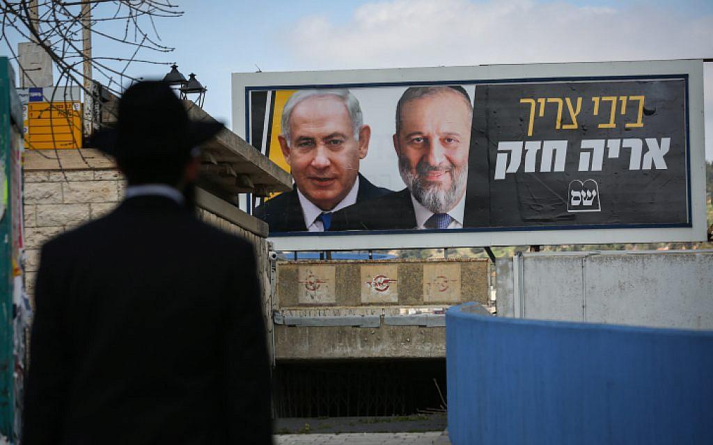 Un Juif ultra-orthodoxe devant un panneau d'affichage avec des photos du Premier ministre Benjamin Netanyahu et du chef du Shas Aryeh Deri, dans le cadre de la campagne électorale Shas, à Safed, le 10 mars 2019. (David Cohen/Flash90)