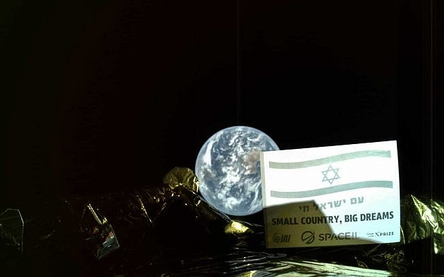 """La photo prise par la sonde Bereshit : une plaque installée sur la paroi externe de la sonde arbore le drapeau national israélien et les phrases """"Am Yisrael Hai"""" (Vive le peuple d'Israël) et """"Petit pays, grands rêves"""", avec le globe terrestre en arrière plan. (Crédit :SpaceIL/IAI)"""