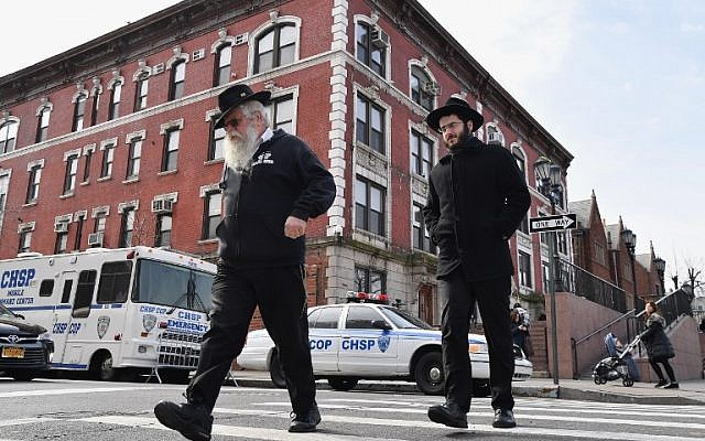 "Deux Juifs orthodoxes passent à côté de véhicules de sécurité de la patrouille ""Crown Heights Shmira Patrol"" dans le quartier de Crown Heights, le 27 février 2019 à New York. (Crédit : Angela Weiss / AFP)"