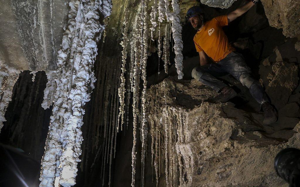 Efi Cohen, membre de l'équipe de recherche de l'Université hébraïque de Jérusalem, au dessus d'un rocher dans l'une des chambres de la grotte de sel de Malham, le 27 mars 2019. (Crédit : Johanna Chisholm/Times of Israel)