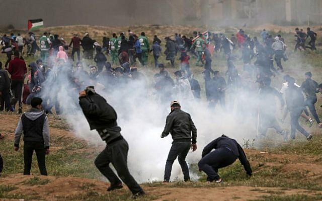 """Des manifestants palestiniens courent se mettre à l'abri de gaz lacrymogène tirés par l'armée israélienne lors des affrontements qui ont suivi une manifestation marquant le premier anniversaire des manifestations violentes de la """"Marche du retour"""", à proximité de la frontière avec Israël à l'est de Gaza ville le 30 mars 2019. (Mahmud Hams/AFP)"""