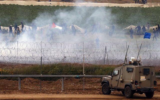 """Des véhicules de l'armée israélienne sont positionnés à la barrière de sécurité à la frontière alors que des Palestiniens agitent des drapeaux nationaux pour marquer le premier anniversaire des manifestations violentes de la """"Marche du Retour"""", le 30 mars 2019. (Jack Guez/AFP)"""