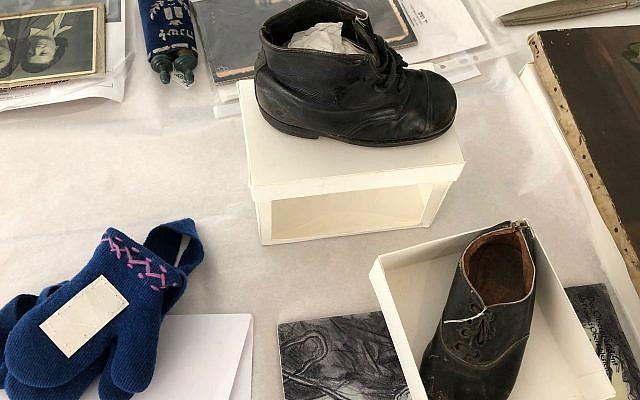 """Une chaussure et des gants ayant appartenu à Hinda Cohen, deux ans, tuée à  Auschwitz le 27 mars 1944. Son père Dov avait écrit la date en découvrant que sa fillette avait été raflée durant une 'Aktion Enfants"""". (Crédit : Amanda Borschel-Dan/Times of Israel)"""