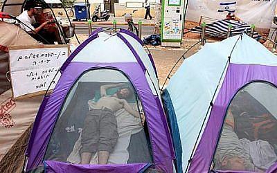 De jeunes Israéliens près de tentes montées sur l'avenue Rothschild de Tel Aviv. Las des prix du logement dans le pays, des milliers de personnes ont dressé une ville de tentes en jurant d'y rester jusqu'à ce que le gouvernement présente une solution, en août 2011 (Crédit :Liron Almog/Flash90/File)