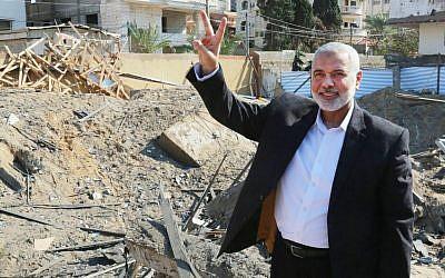 Le chef du bureau politique du Hamas Ismail Haniyeh fait le V de la victoire sur les décombres de son bureau, détruit par une frappe de l'armée israélienne, le 27 mars 2019. (Crédit : Hamas)