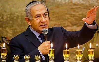 Le Premier ministre Benjamin Netanyahu, à gauche, s'exprime pendant une cérémonie d'allumage de bougies à l'occasion de la fête de Hanoukkah, au mur Occidental, dans la Vieille ville de Jérusalem, le 6 décembre 2018 (Crédit : Gil Cohen-Magen/Pool/AFP)