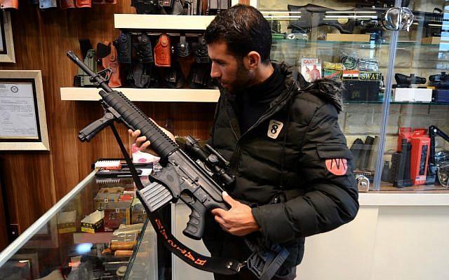 Un client inspecte un fusil vendu dans une armurerie à Mossoul, dans le nord de l'Irak, le 28 janvier 2019. (Crédit photo : Zaid AL-OBEIDI / AFP)