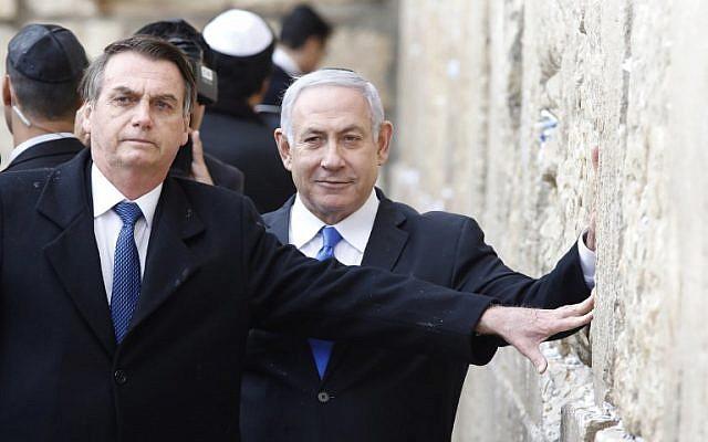 Le président brésilien Jair Bolsonaro (à gauche) et le Premier ministre Benjamin Netanyahu touchent le mur Occidental, le lieu le plus saint où les Juifs peuvent prier, dans la Vieille Ville de Jérusalem, le 1er avril 2019. (Crédit : Menahem KAHANA / POOL / AFP)