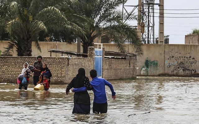 Une famille iranienne dans le village inondé d'Ahvaz, le31 mars 2019  (Crédit : Mehdi Pedramkhoo / TASNIM NEWS / AFP)