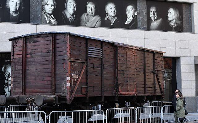 Des portraits des survivants de la Shaoh sur un wagon de train de déportation au Museum of Jewish Heritage à New York, le 2 avril 2019. (Crédit : TIMOTHY A. CLARY / AFP)