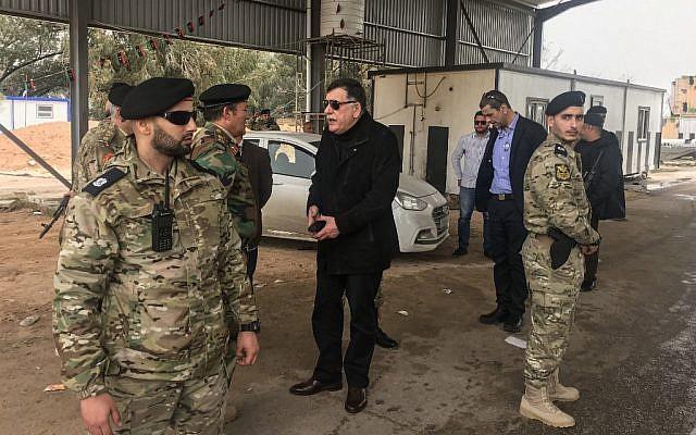 Le chef du gouvernement unitaire soutenu par l'ONU Fayez al-Sarraj, au centre, visite les commandants militaires et sécuritaires qui ont supervisé la re-capture du checkpoint 27 à Janzour, entre Tripoli et Zawiya, le 5 avril 2019 (Crédit :  Mahmud TURKIA / AFP)