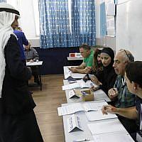 Un Arabe israélien se prépare à voter aux élections parlementaires israéliennes dans un bureau de vote installé dans une école à Taibé, dans le nord du pays, le 9 avril 2019. (Crédit : Ahmad Gharabli/AFP)