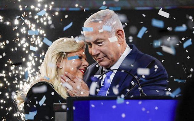 Le Premier ministre Benjamin Netanyahu embrasse son épouse Sara au milieu de confettis lors de son discours de victoire devant des sympathisants au siège du Likud à Tel Aviv, après les élections du 9 avril 2019. (Thomas Coex/AFP)