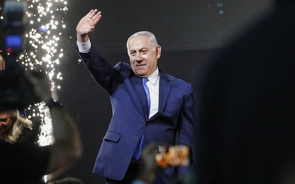 Le Premier ministre Benjamin Netanyahu salue les partisans au siège du parti du Likud, dans la ville côtière de Tel Aviv, lors de la soirée électorale dans la nuit du 10 avril 2019 (Crédit : Thomas Coex / AFP).